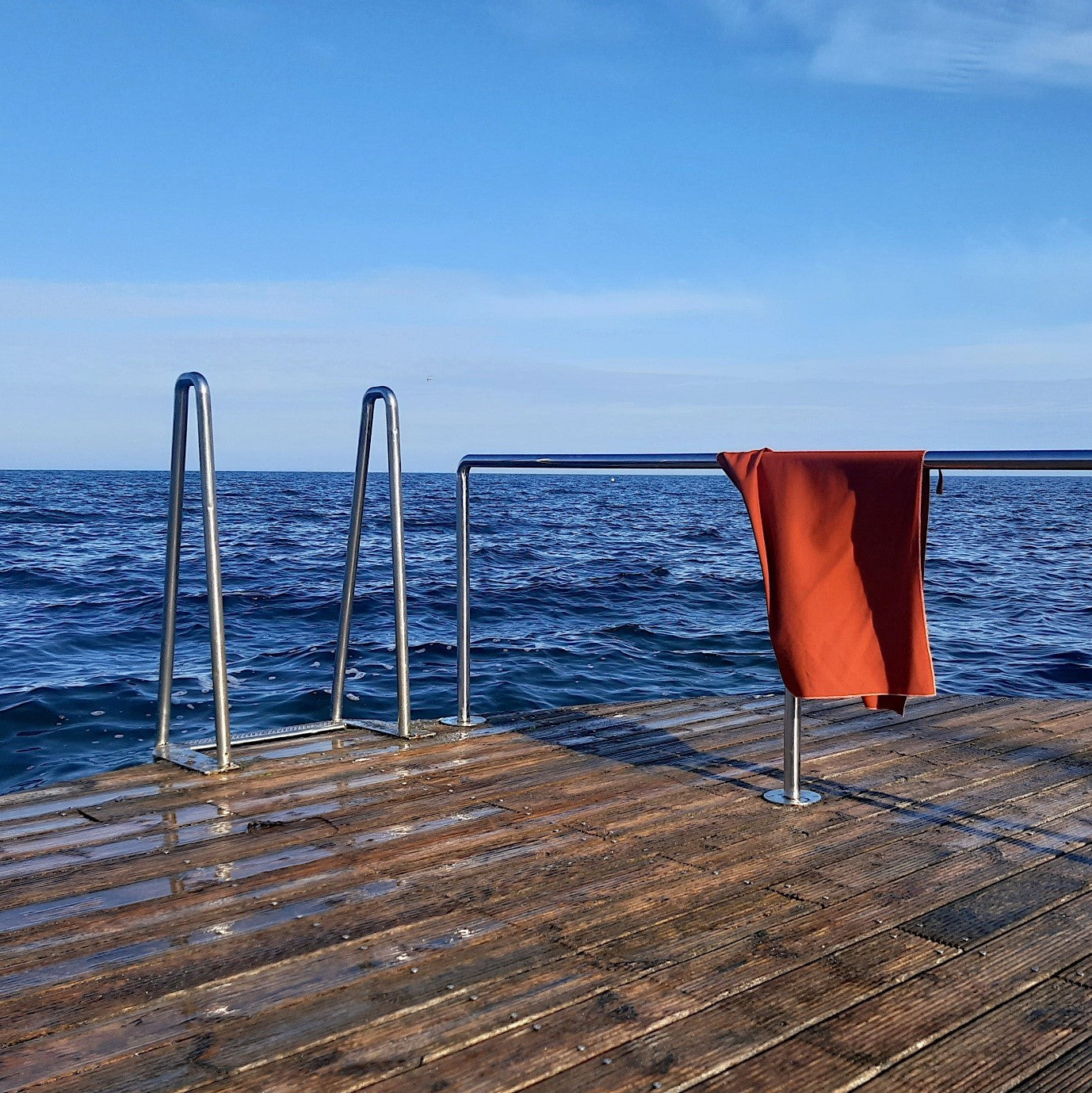 Raw Silk Travel Towel Hanging on Bathing Jetty by the Sea, Chili Oil Color, No Microfibre Microplastic, Sustainable Travel Outdoor Swimming Camping Hiking Backpacking | SHIN JARDBO