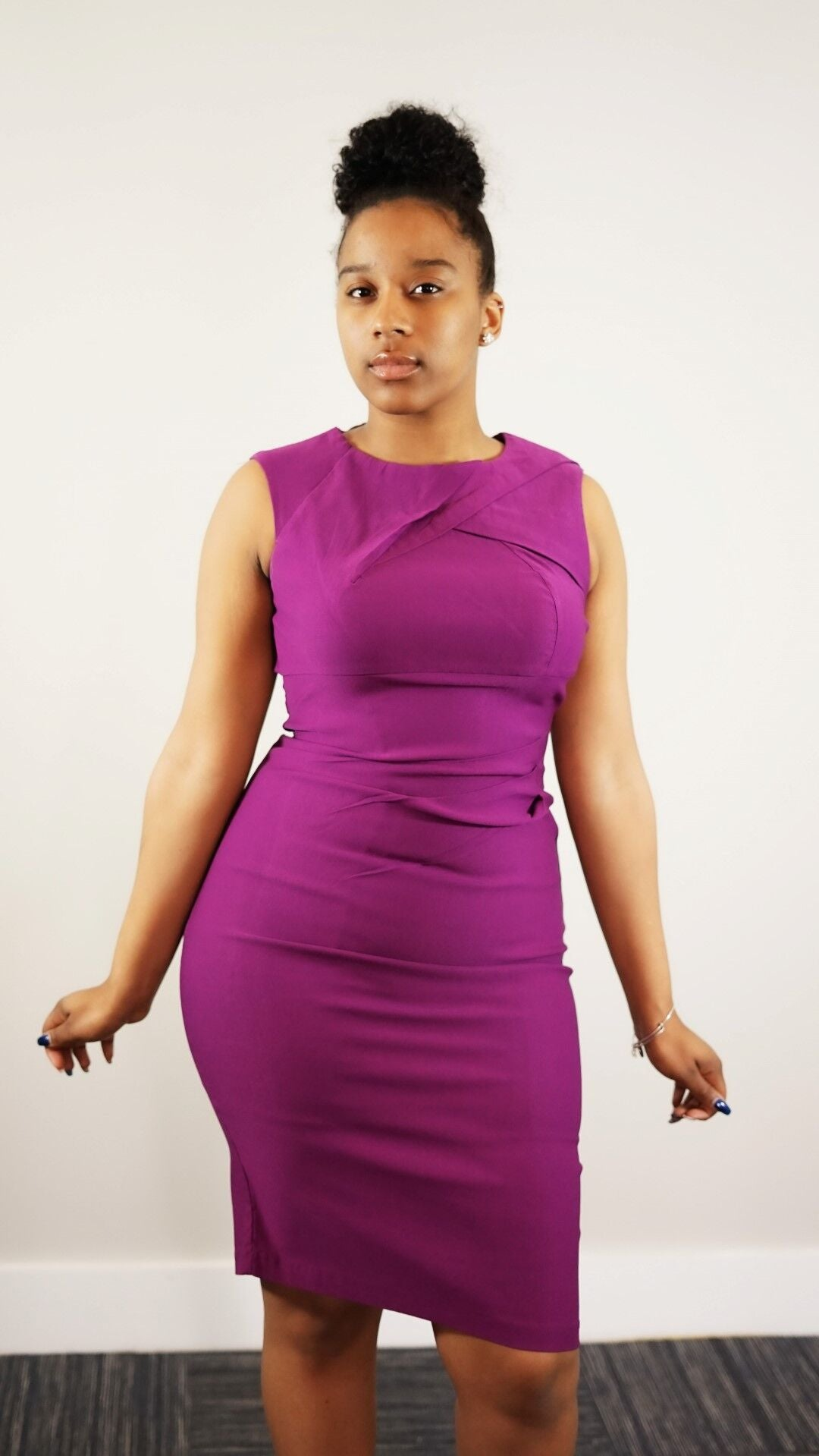 Front knee up view of plus size model in a purple Pleated Super Stretch Pencil Dress