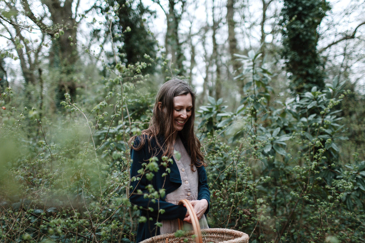 Rebecca Desnos standing in the woods carrying a basket to gather nettles for her dye pot. Rebecca is a natural dyer based in the UK.