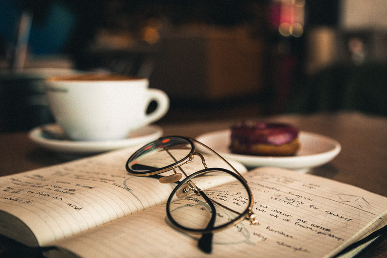Eyeglasses on top of notebook in a Phil & Sebastian coffee shop