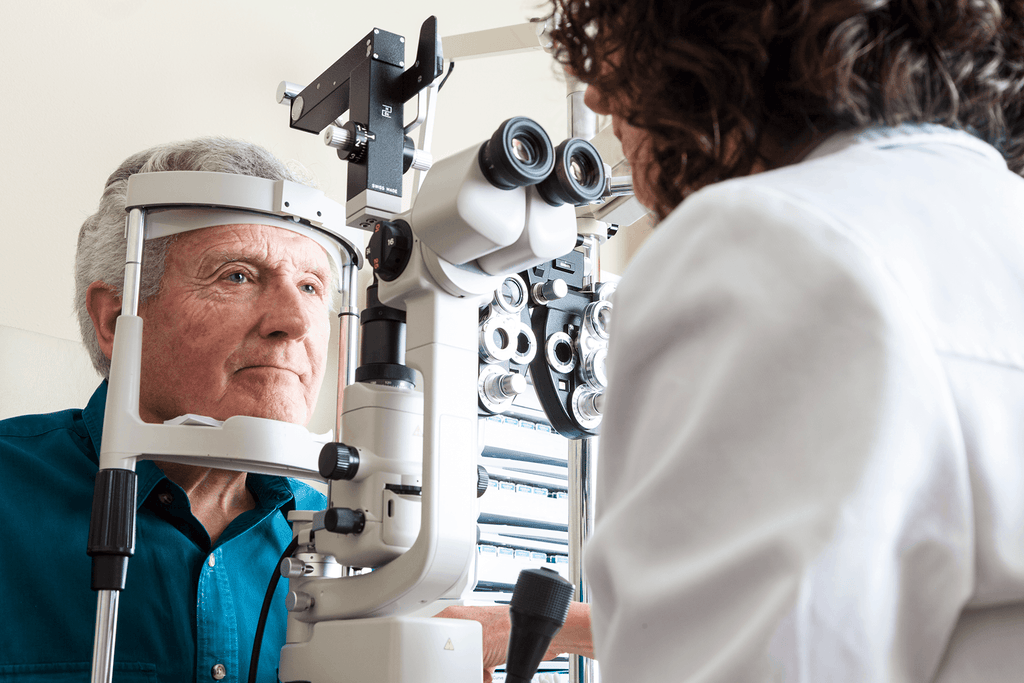 Elderly gentleman getting an eye assessment for refractive surgery on his eyes