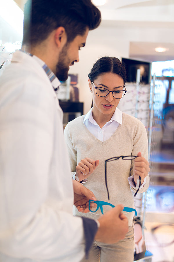 An optician helps a patient select prescription eyeglasses