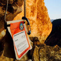 mountain espresso bag hanging from sandstone cliff with pine trees in the background