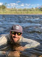 Guy in river wearing charcoal 5 panel hat in Colorado