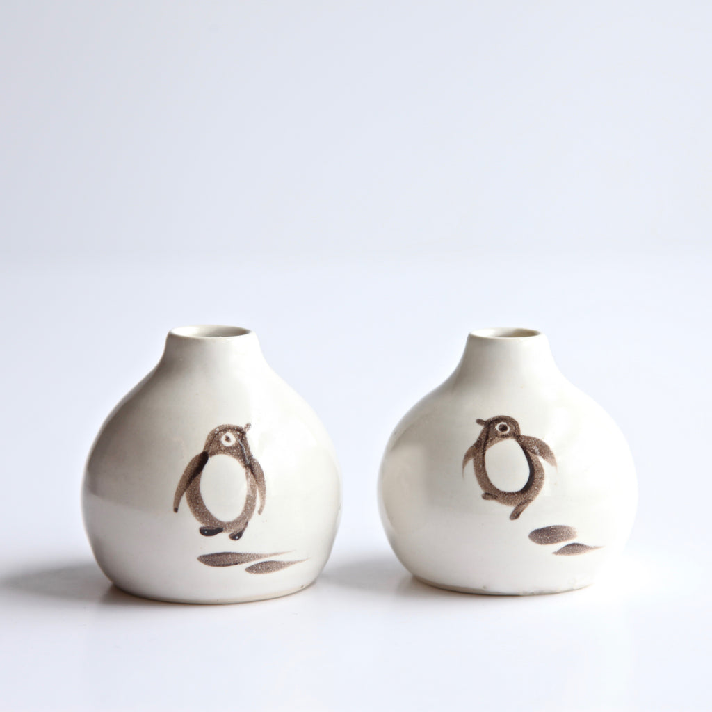 A pair of small bud vases with hopping Gentoo penguins painted in black