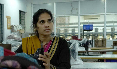 Talented female sewing machine operator in factory.