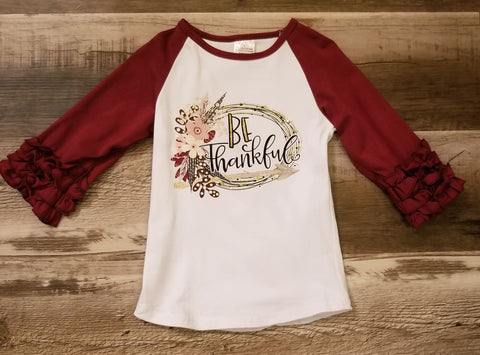 "Burgundy icing ruffle sleeves raglan top with ""Be Thankful"" words on front."