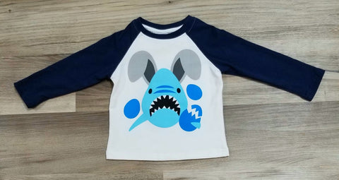 White top with blue baseball style sleeves with graphic of shark with bunny ears breaking eggs.