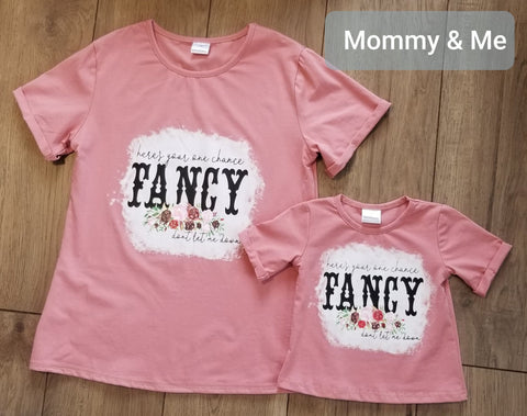 "Dusty rose short sleeve top in mommy and me sizes.  Front has screen of ""here's your one chance Fancy don't let me down""."