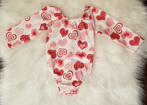 Buttery soft white leo with pink and red assorted hearts throughout.  Snap closure, scoop back.