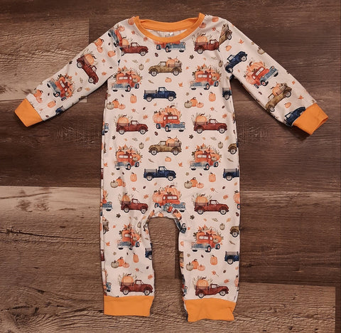 White romper with multiple styles and colors of trucks hauling pumpkins.  Neck, sleeve and foot feature orange trim.