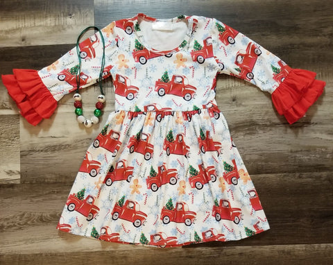 Buttery soft white dress with red truck hauling a Christmas tree print throughout.  The print also has gingerbread men, candy canes and snowflakes throughout.  The long sleeves are accented with double ruffles in red.