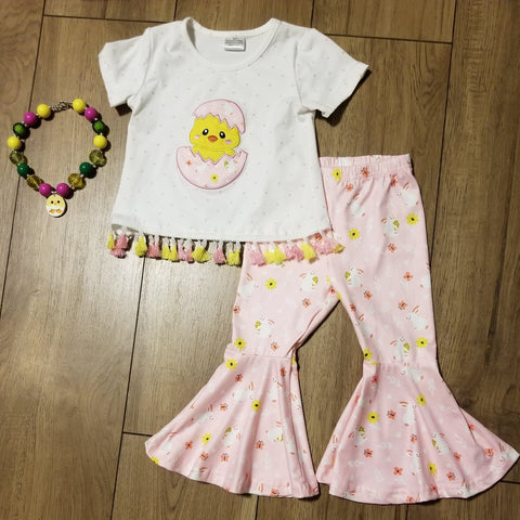 White short sleeve top with tassels on bottom.  Front has a baby chic applique cracking out of an egg.  Pink bell bottom pants have a bunny print.