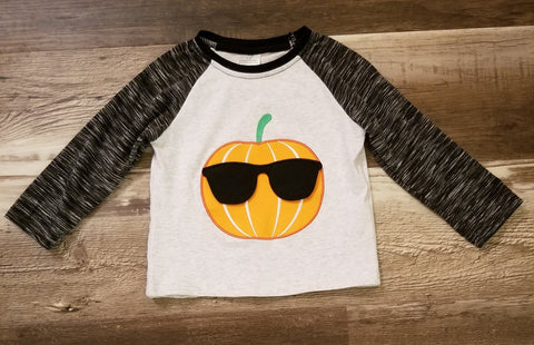 This Boys top features black and grey heather sleeves, and a pumpkin on the front wearing black sunglasses.