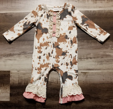 Cream colored baby girl romper with a brown spotted cow print.  Lace trim on bodice with button accent, and pink and lace ruffle at ankle.