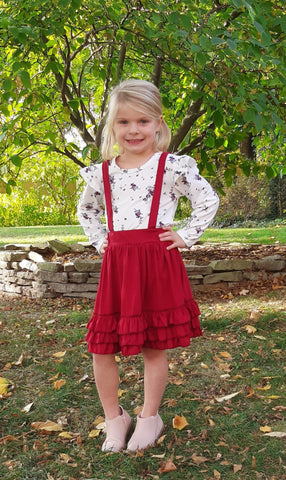 Burgundy ruffle suspender skirt with white long sleeve top with floral print.