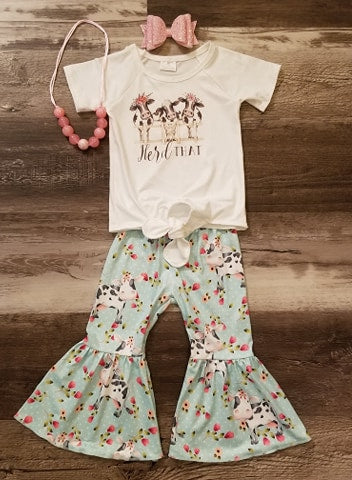 "Two piece set features a short sleeve front tie white front tie top with cows and words ""Herd That"" underneath along with mint bell bottom pants with a cow and floral pattern."