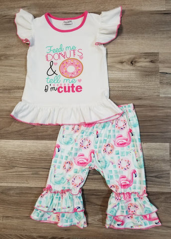 "White flutter sleeve top with phrase ""Feed Me Donuts & tell me I'm cute"" on the front with a sprinkled donut.  Capris are mint green with donuts, flamingo and unicorn floaties."