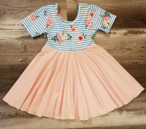 This milk-silk dress has blue stripes with a floral pattern on the top, and the twirling skirt is a light peach color.