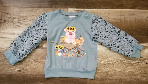 Blue long sleeve top with crochet lace sleeves features a pig in a wheel barrel with pumpkins and a sunflower head wrap.
