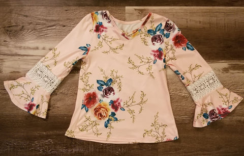 Light pink floral print  bell sleeve long sleeve top with criss cross neckline, and lace detail on sleeve.