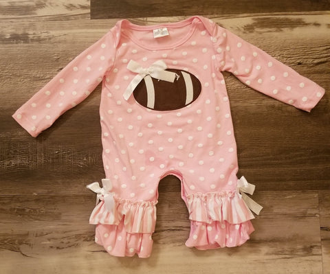 Pink baby girl romper with white polka dots, a football qpplique on front, and ruffle detail at ankles.