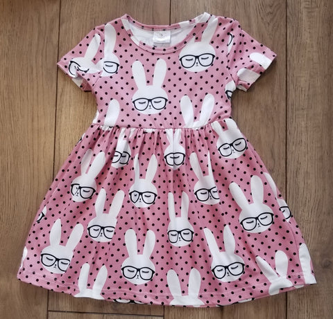Dusty rose short sleeve dress with black polka dots and bunny heads wearing glasses.