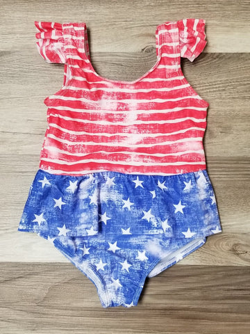 Girls one piece swimsuit.  Top portion has faded red and white stripes.  Shoulder has a ruffle, and middle has a ruffle.  Bottom portion is faded blue with stars.