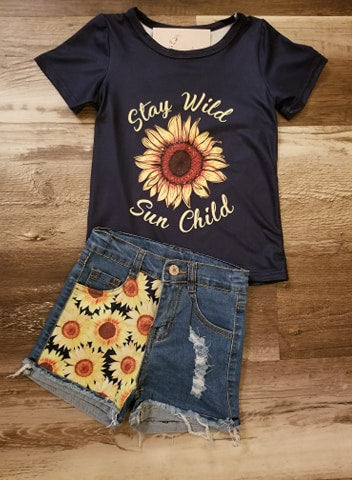 "Navy blue short sleeve shirt with sunflower on middle and the words ""Stay Wild Sun Child"" around it, paired with denim jean shorts with sunflower print on one leg and a distressed hemline."