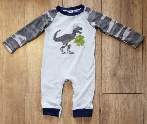 Baby boy romper in light grey with camo print dinosaur carrying a clover on front.  Long sleeves are in coordinating camo print.