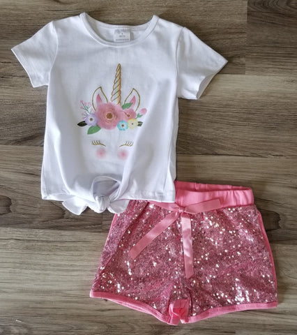 White short sleeve top with unicorn print on front, paired with pink sequin shorts.