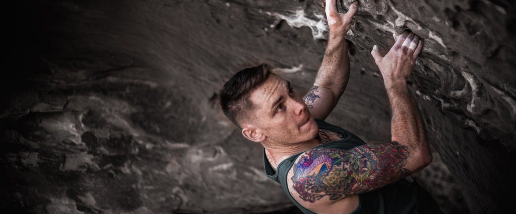 Chris Simmons Bouldering and showing off his Tattoo