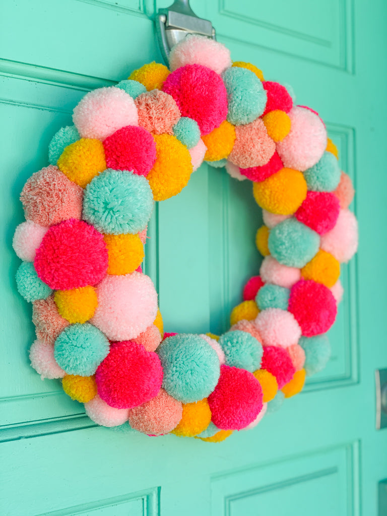 Colorful pom pom Christmas wreath hanging on turquoise door
