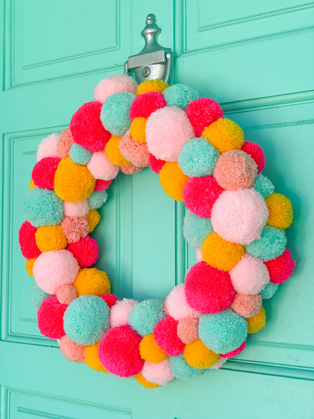 Colorful pom pom Christmas wreath hanging on turquoise front door.