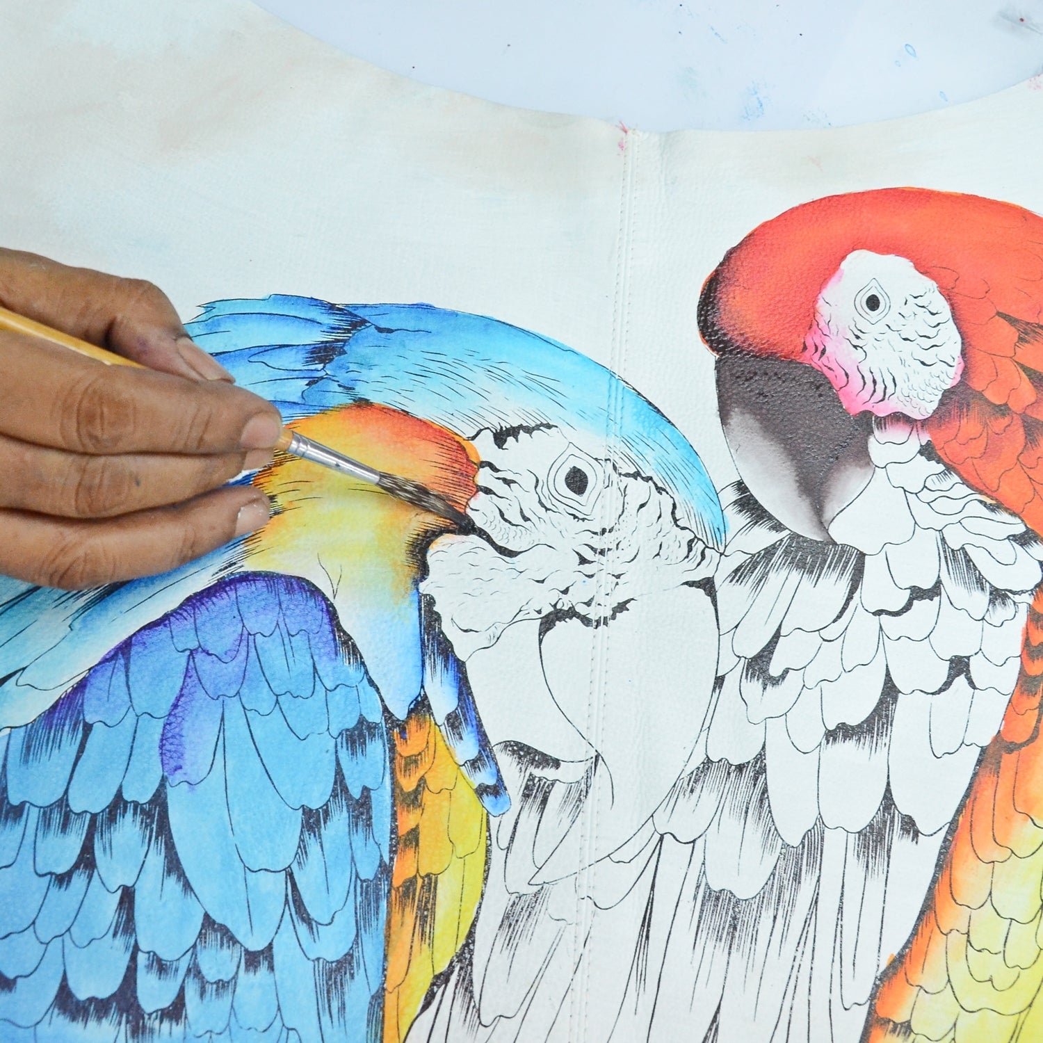 Parrots being painted on leather at Anuschka