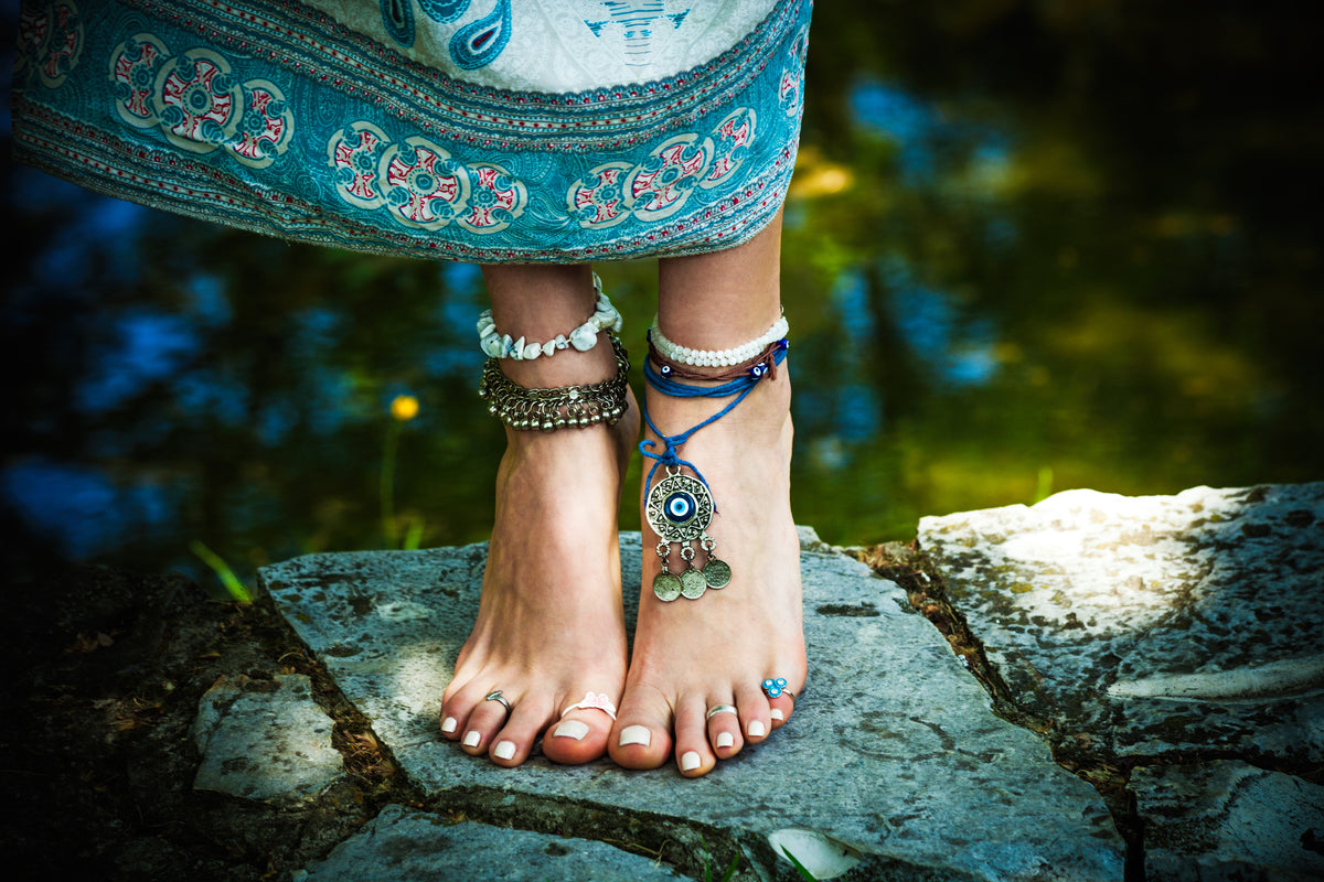 woman summer boho fashion style barefoot with jewelry anklets and rings stand on stone outdoor summer day