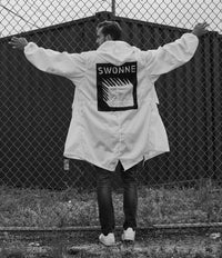 White fishtail parka, hand painted, limited edition, one of a kind, painted in Brooklyn, Swonne logo, model climbing fence, wearing Swonne Jeans