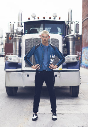 model standing in front of truck, wearing moto jacket, hand painted and limited edition, blue leather with black racing stripes