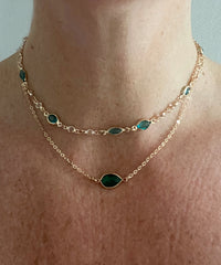 gold necklace with green and crystal gems