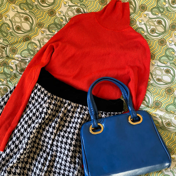 Orange polo neck, dogtooth print skirt and blue handbag, all found at a clothes swap