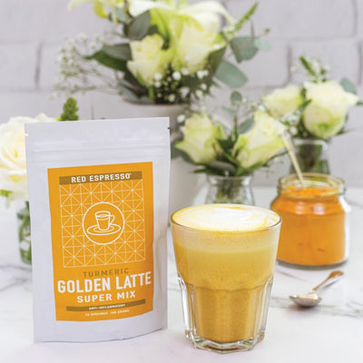 turmeric latte mix product with a beautiful flower behind