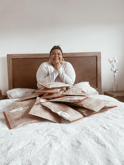 Teresa Bisazza sitting on a bed surrounded by packaged orders