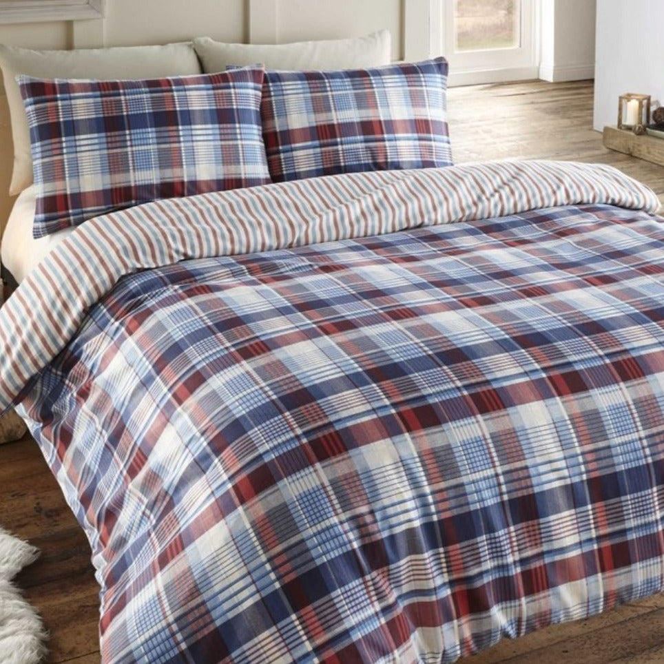 A sumptuous and comforting brushed cotton, flannelette check, with co-ordinating stripe reverse in rich navy blue and red tones