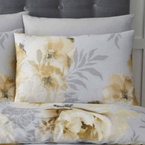 Like a still life painting, oversized Impressionist style ochre yellow blossoms and peonies dramatically sit over a silver grey ground pillowcase