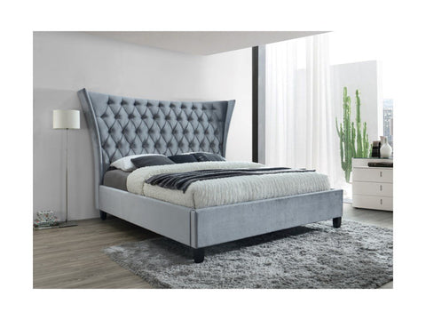 Tufted king size bed with rug under it.