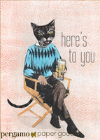 Greeting card of a dressed up cat drinking a beer, text reads here's to you