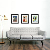 Colorful framed art prints above a modern couch