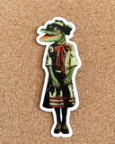 Retro alligator decal on cork background. Alligator is wearing a 1920s style dress.