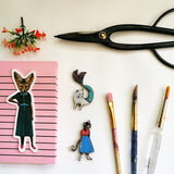 Flat lay of stickers with scissors and paintbrushes. Fox sticker, cat mermaid, cat in a dress