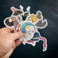 Holding various animal stickers, mermaid cat sticker, illustrated squirrel sticker, otter vinyl sticker, flamingo dude sticker, alligator retro sticker